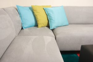 Grey couch with blue and yellow pillows